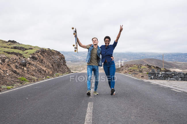 Attractive multicultural young couple with skateboard walking on road with raised arms — Stock Photo