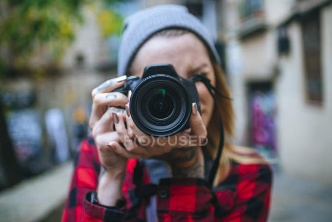 Closeup of tattooed woman taking a photo with a reflex camera — Stock Photo