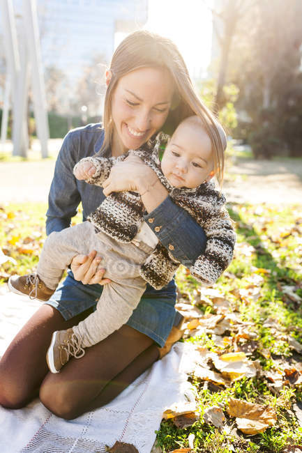 Portrait of young woman holding baby boy on blanket in park — Stock Photo