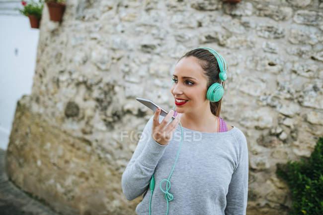 Giovane donna che trasmette un messaggio vocale con un telefono cellulare — Foto stock