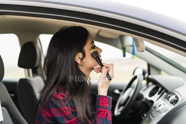 Woman applying make up in car — Stock Photo