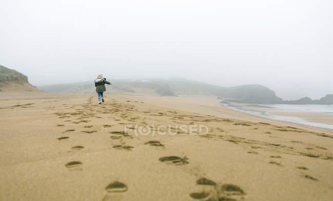 Spagna, Asturie, Veduta posteriore della bambina che corre in spiaggia in una giornata nebbiosa — Foto stock