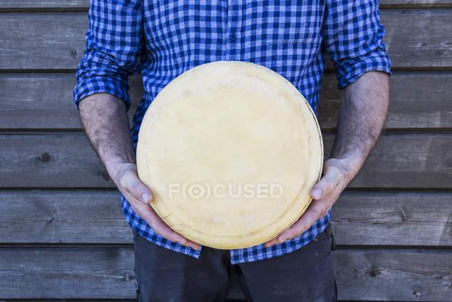 Hombre que sostiene el pan de queso sobre fondo de madera - foto de stock