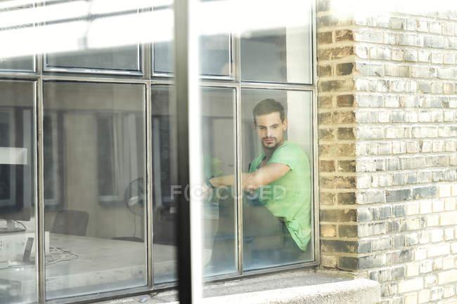 Junge besorgte Berufstätige sitzen am Fenster — Stockfoto