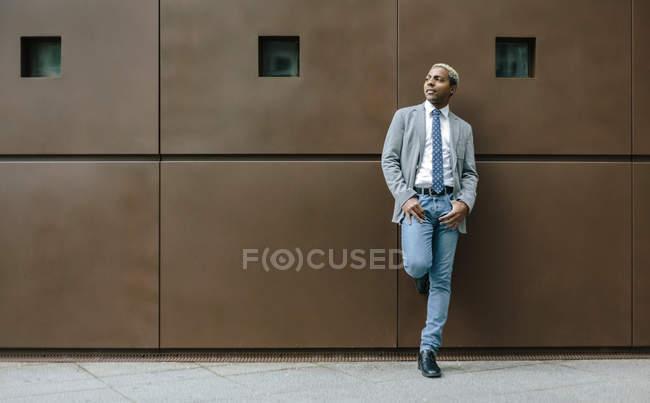 Empresário em frente a parede com as mãos nos bolsos — Fotografia de Stock