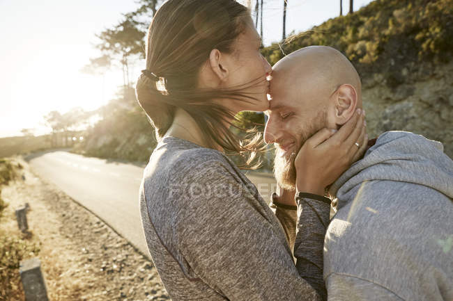 Young woman kissing boyfriend on forehead — Stock Photo