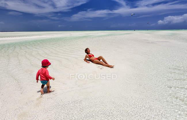 Танзанія, Занзібар острів, Paje, матері і мало донька розслаблюючий під час відливу на пляжі — стокове фото