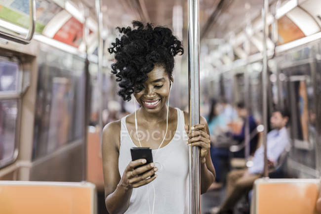 Portrait of woman using smartphone in subway train — Stock Photo