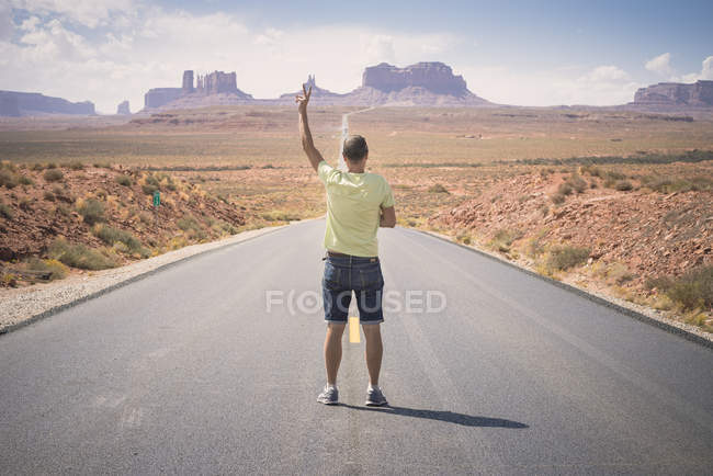 USA, Utah, man standing on road to Monument Valley showing victory sign — Stock Photo