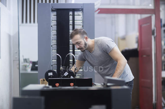 Young man working in printing shop — Stock Photo