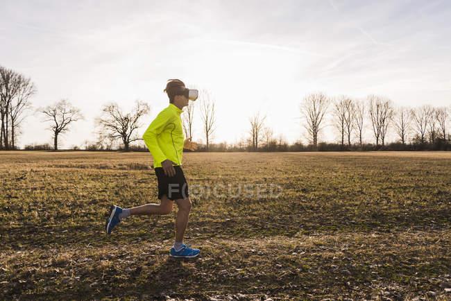 Портрет молодого человека, бегущего в очках виртуальной реальности в поле — стоковое фото