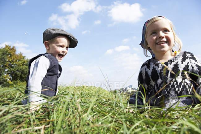 Duas crianças felizes sentadas no prado — Fotografia de Stock