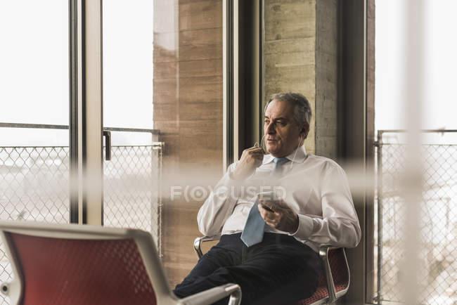 Менеджер сидит на стуле в офисе — стоковое фото