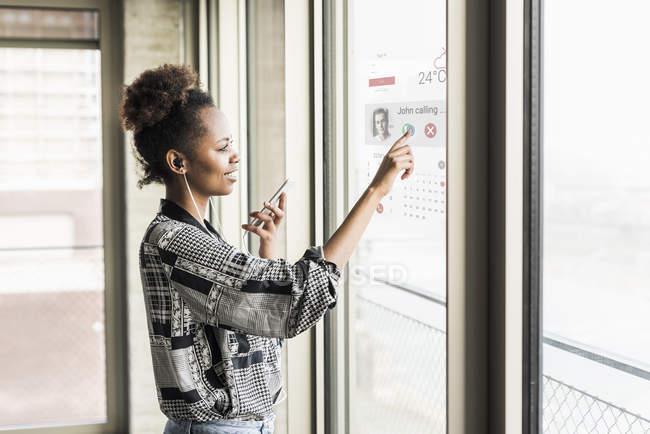 Portrait of businesswoman using glass screen — Stock Photo