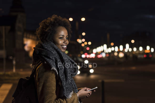 Portrait of smiling young woman with smartphone at roadside — Stock Photo
