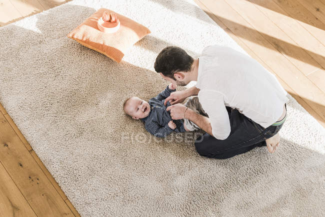 Father changing diapers and playing with baby son on carpet — Stock Photo