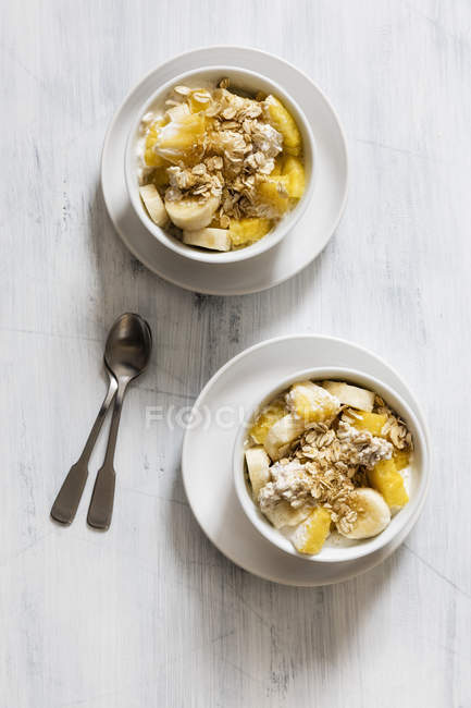 Top view of oat flakes with sliced banana and yogurt in bowls — Stock Photo
