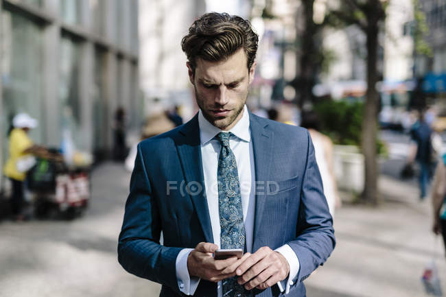 Retrato del hombre de negocios utilizando el teléfono inteligente en la calle - foto de stock