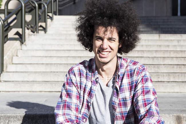 Портрет усміхнений юнак, сидячи на сходах — стокове фото