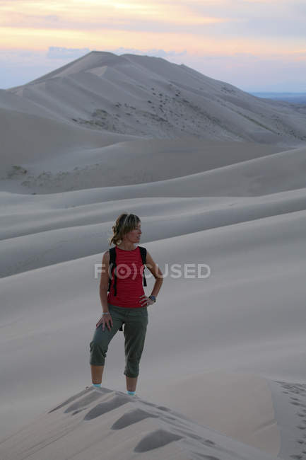 Woman standing on sand dunes in desert — Stock Photo