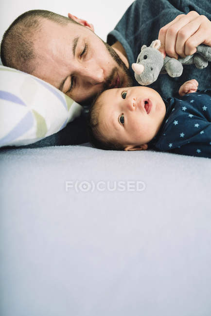 Father playing with newborn baby girl and stuffed rhino on bed — Stock Photo