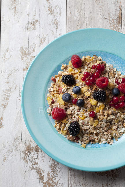 Top view of oat flakes with berries on blue plate — Stock Photo