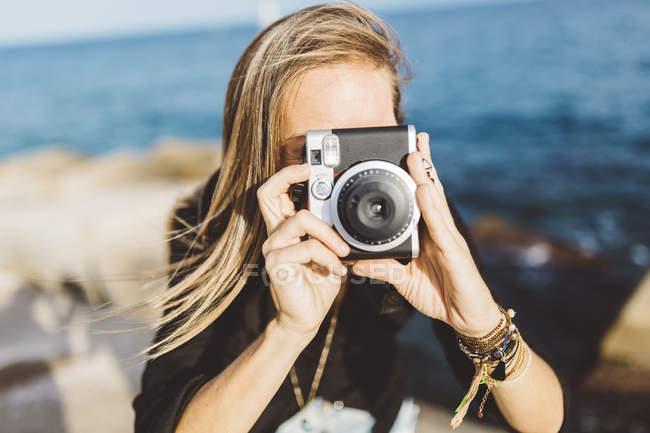 Молодая женщина фотографируется со старомодной камерой на берегу моря — стоковое фото