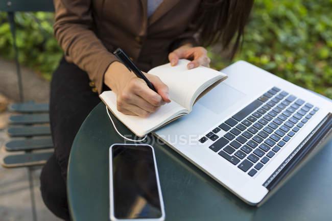 Молода жінка, писати в ноутбук сидять ноутбук з смартфон — стокове фото