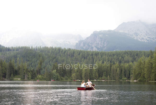 Young couple in rowing boat on lake — Stock Photo