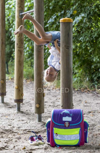 Menina com bolsa escola na barra alta do parque a sorrir — Fotografia de Stock