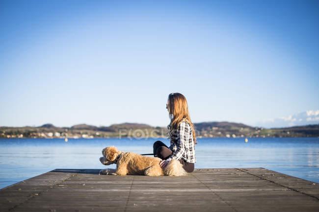 Frau mit Hund auf Pier, Seelandschaft auf Hintergrund — Stockfoto