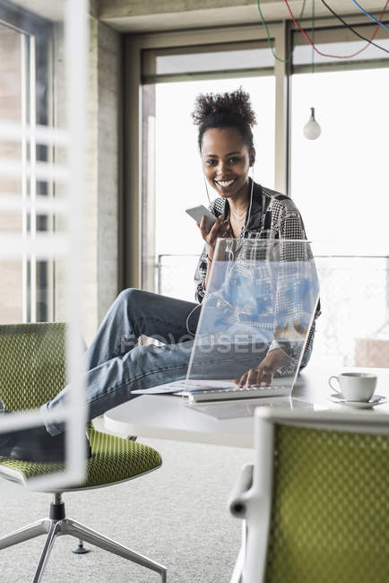Woman working in office with transparent computer — Stock Photo