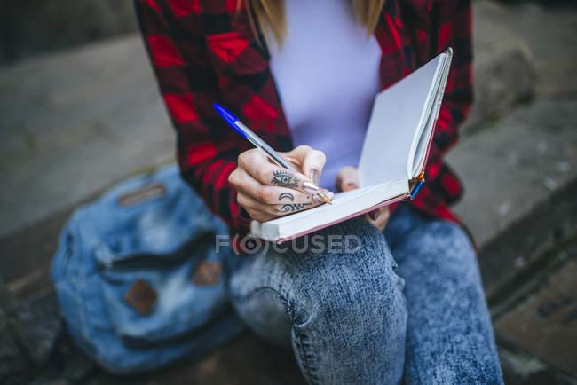 Крупним планом жінка Татуйовані руки набравши в Блокноті. — стокове фото