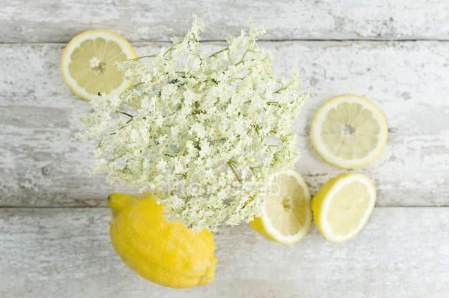 Нарезанный и весь лимоны и elderflowers на белом потрепанный древесины — стоковое фото
