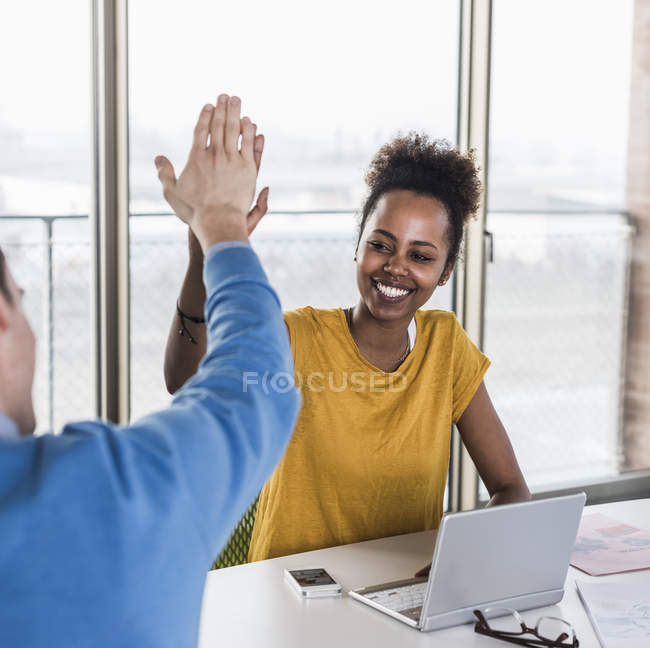 Portrait of young business colleagues high fiving — Stock Photo