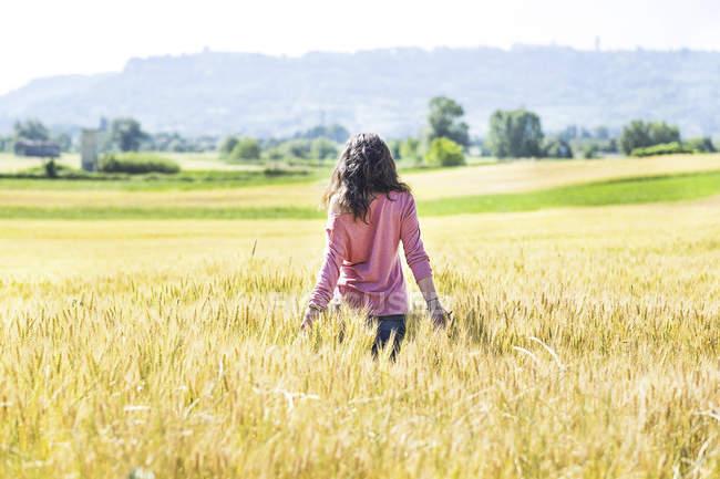 Jovem mulher de pé no campo de grãos — Fotografia de Stock