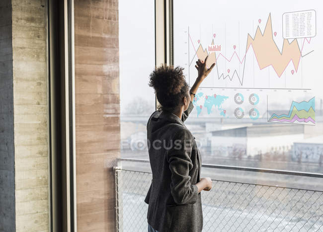 Portrait of businesswoman touching glass screen — Stock Photo