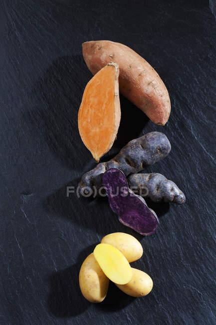 Closeup view of three sorts of raw potatoes on black background — Stock Photo