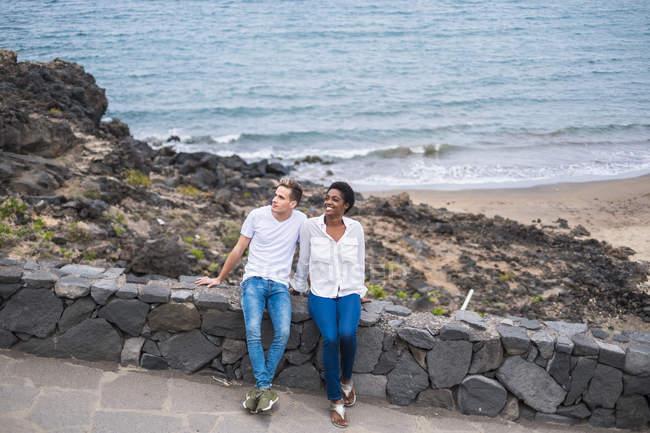 Attraktives multikulturelles junges Paar sitzt am Zaun am Strand — Stockfoto