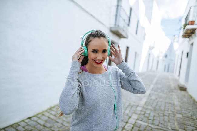 Spain, Andalusia, Vejer de la Frontera, Young woman listening to music wearing sports clothing — Stock Photo