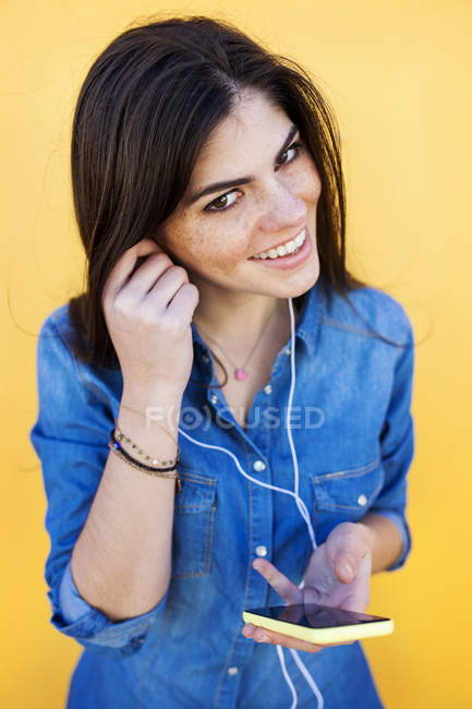 Woman standing with earphones and smartphone — Stock Photo