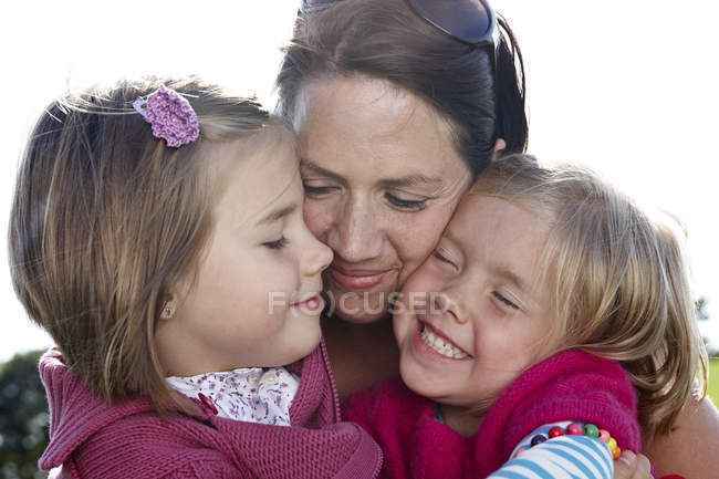Mother hugging two girls outdoors — Stock Photo