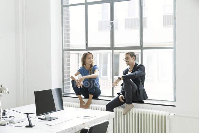 Колеги, сидячи на підвіконні і говорити в офісі — стокове фото