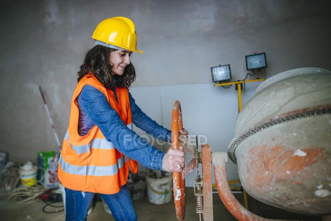 Femme travaillant avec une bétonnière . — Photo de stock