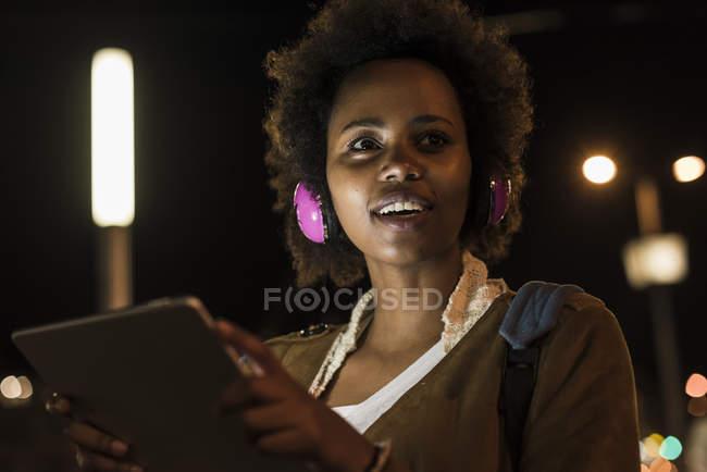 Jovem com fones de ouvido e tablet à noite — Fotografia de Stock
