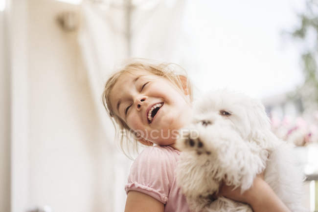 Happy girl playing with cute little dog — Stock Photo