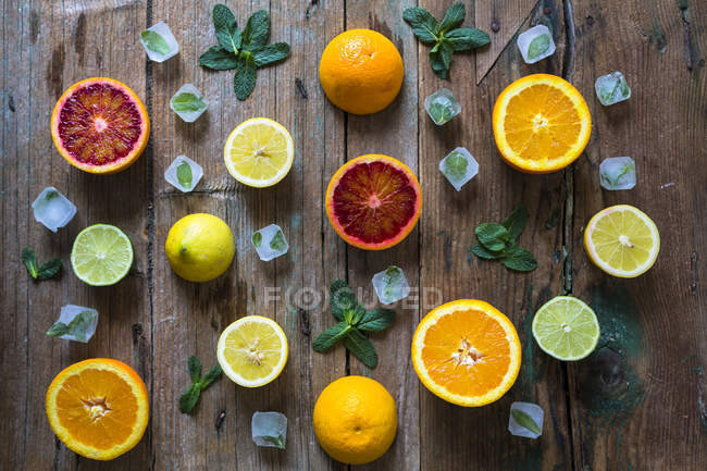 Vue de dessus des moitiés de fruit différent avec des cubes de glace et de feuilles de menthe — Photo de stock