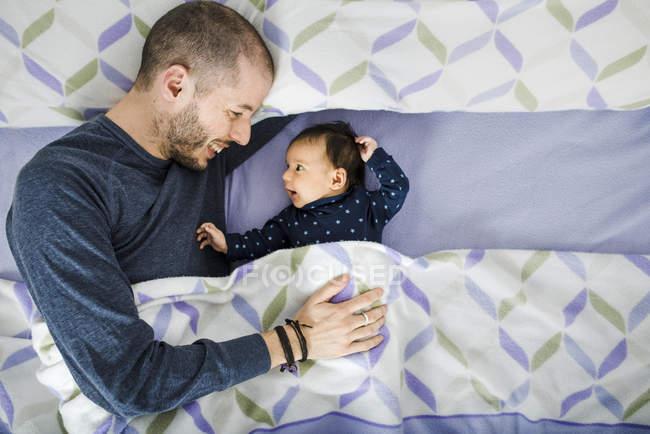 Bébé fille heureux couché dans le lit avec père — Photo de stock