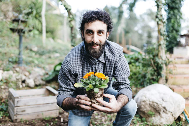 Gardener with plant in his hand — Stock Photo