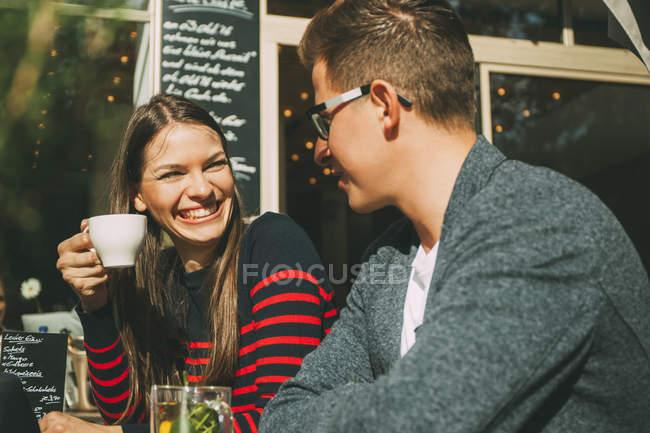 Улыбающаяся пара, сидящая в кафе и разговаривающая — стоковое фото